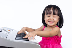 Happy Asian Chinese little girl playing electric piano keyboard Stock Photos