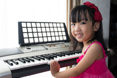 Happy Asian Chinese little girl playing electric piano keyboard Royalty Free Stock Images