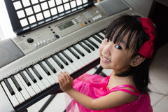 Happy Asian Chinese little girl playing electric piano keyboard Stock Photo