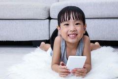 Happy Asian Chinese little girl playing phone on the floor Royalty Free Stock Images