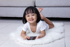 Happy Asian Chinese little girl playing phone on the floor Royalty Free Stock Photo