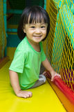 Happy Asian Chinese little girl playing slide at indoor playgrou Royalty Free Stock Photos