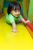 Happy Asian Chinese little girl playing slide at indoor playgrou Stock Image