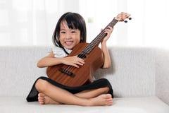 Happy Asian Chinese little girl playing ukele Stock Image