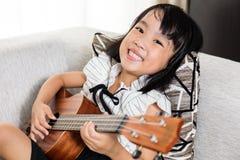 Happy Asian Chinese little girl playing ukele Stock Photography
