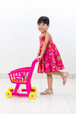 Happy Asian Chinese little girl pushing toy trolley Royalty Free Stock Image