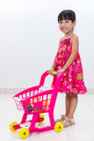 Happy Asian Chinese little girl pushing toy trolley Stock Image