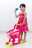 Happy Asian Chinese little girl pushing trolley holding credit c. Happy Asian Chinese little girl pushing toy trolley holding credit card in isolated white Royalty Free Stock Photo