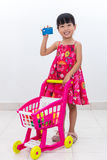 Happy Asian Chinese little girl pushing trolley holding credit c. Happy Asian Chinese little girl pushing toy trolley holding credit card in  white background Royalty Free Stock Photos