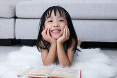 Happy Asian Chinese little girl reading book on the floor Stock Image