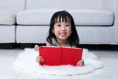 Happy Asian Chinese little girl reading book on the floor Royalty Free Stock Photo