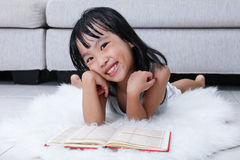 Happy Asian Chinese little girl reading book on the floor Royalty Free Stock Photos