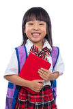 Happy Asian Chinese little girl with school bag and book Royalty Free Stock Photography