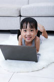 Happy Asian Chinese little girl using laptop on the floor Stock Photography