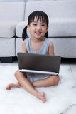 Happy Asian Chinese little girl using laptop on the floor Stock Photos