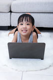 Happy Asian Chinese little girl using laptop on the floor Royalty Free Stock Photos