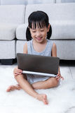 Happy Asian Chinese little girl using laptop on the floor Stock Photo