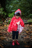 Happy Asian Chinese little girl wearing raincoat in forest Royalty Free Stock Photography
