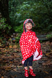 Happy Asian Chinese little girl wearing raincoat in forest Royalty Free Stock Image