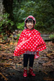 Happy Asian Chinese little girl wearing raincoat in forest Royalty Free Stock Photos