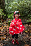 Happy Asian Chinese little girl wearing raincoat in forest Stock Images