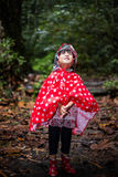 Happy Asian Chinese little girl wearing raincoat in forest Stock Image