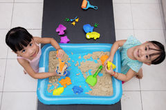 Happy Asian Chinese little girls playing kinetic sand at home Stock Photography