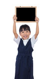 Happy Asian Chinese little primary school girl holding chalkboar Royalty Free Stock Photos