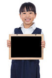 Happy Asian Chinese little primary school girl holding chalkboar Royalty Free Stock Image