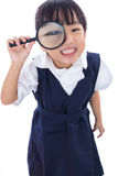 Happy Asian Chinese little primary school girl holding magnifyin Stock Photos