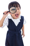 Happy Asian Chinese little primary school girl holding magnifyin Stock Image