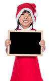 Happy Asian Chinese little santa girl holding blank board Royalty Free Stock Image