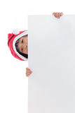 Happy Asian Chinese little santa girl peeking behind blank board. In isolated wihte background royalty free stock images