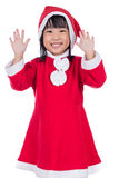 Happy Asian Chinese little santa girl waving hands Stock Image