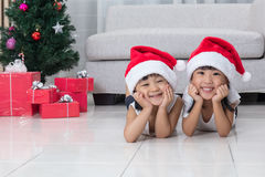 Happy Asian Chinese little sisters celebrate Christmas holiday a. T home beside Christmas tree and gift box in the living room royalty free stock photography