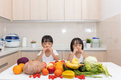 Happy Asian Chinese little sisters eating fruit and vegetable Stock Photo
