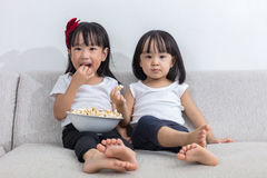 Happy Asian Chinese little sisters eating popcorn on the sofa Royalty Free Stock Image