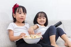 Happy Asian Chinese little sisters eating popcorn on the sofa Stock Photography