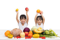 Happy Asian Chinese little sisters with fruit and vegetable. In isolated white background stock photos