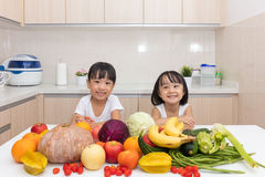 Happy Asian Chinese little sisters with fruit and vegetable. In the kitchen at home royalty free stock photo