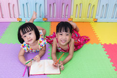 Happy Asian Chinese little sisters laying on the floor coloring Stock Photo