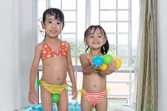 Happy Asian Chinese little sisters playing in the inflatable poo Royalty Free Stock Photography