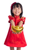 Happy Asian Chinese little wearing cheongsam and holding gold in Royalty Free Stock Photo