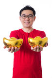 Happy Asian Chinese man wearing red shirt holding ingot Royalty Free Stock Photos