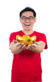 Happy Asian Chinese man wearing red shirt holding ingot Stock Photo