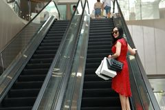 Happy Asian Chinese modern fashionable woman shopping bags in a mall store wear sunglasses casual buyer smile laugh elevator lift. There is a Asian Chinese royalty free stock image