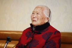 Sad Elderly Asian Chinese 90s old woman portrait. Happy Asian Chinese old woman, 93 years old, up to 90s , silvery hair, golden earing on her ear Stock Images