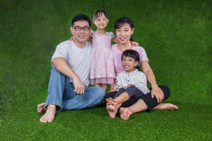 Happy Asian Chinese parents and daughters sitting on the grass Royalty Free Stock Photo