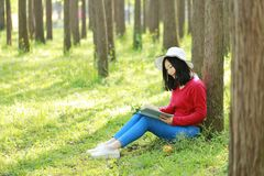 Happy Asian Chinese woman beauty girl smile and read a book in forest spring park lean on a tree stock photography