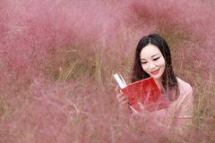 Happy Asian Chinese woman girl feel freedom sweet dream pray flower field autumn fall park grass lawn hope nature read book school. Pink colour grass lawn, rose royalty free stock photography